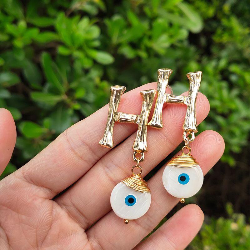 hot-selling gold letter earrings hand-woven devil's eye pendant earrings wholesale nihaojewelry NHAN241915